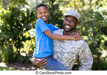 African American man wearing a military uniform holding his son