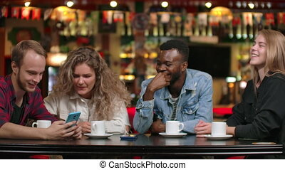 African-American man with a girl looking at a smartphone and...