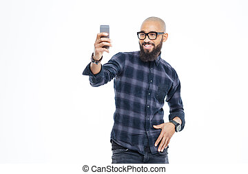 African american man with beard smiling and taking selfie