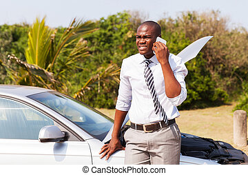african american man with broken down car calling for help