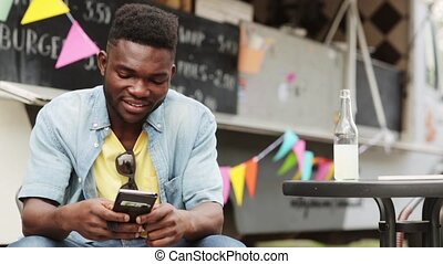 african american man with smartphone at food truck -...