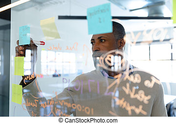 African American man writing on sticky notes