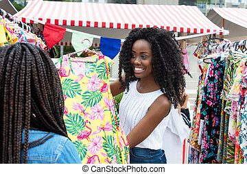 African american market vendor presenting clothes