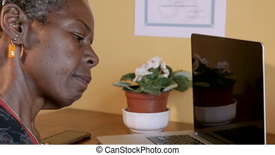 African American mature woman thinking and writing while...