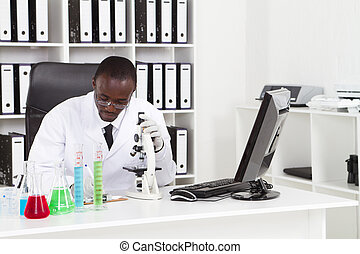 african american medical scientist wearing lab coat with...