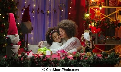 African American mom and little daughter exchange gifts and unpack boxes with anticipation of a surprise. Woman and girl sitting near the Christmas tree against the background of the home room decorated for a festive night. Happy family portrait, New Year celebration concept.