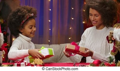 African American mom and little daughter in white sweaters exchange gifts and unpack boxes with anticipation of a surprise. Woman and a girl sit against the background of the home room, decorated for the Christmas holidays. Happy family portrait, New Years celebration concept. Close up.