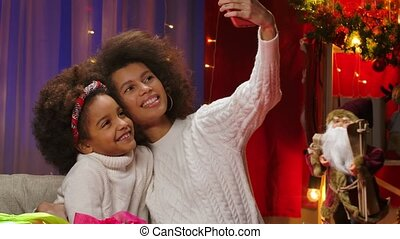 African American mom and little daughter in white sweaters having fun posing and taking selfie on smartphone. Happy family portrait, New Years celebration concept. Close up.