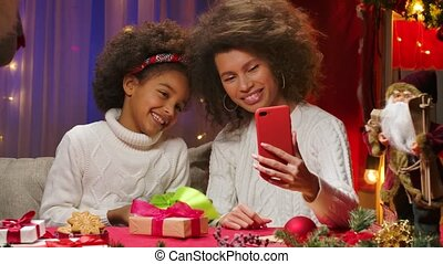 African American mom and little daughter in white sweaters talking via video call on their smartphone. Happy family portrait, New Years celebration concept. Close up.
