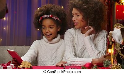 African American mom and little daughter in white sweaters talking via video call on their tablet. Happy family portrait, New Years celebration concept. Close up.