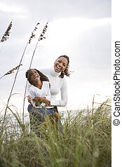 African-American mother and daughter laughing at beach