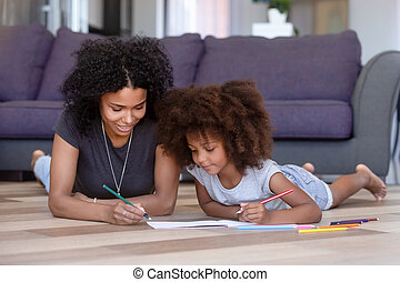 African American mother coloring with daughter, lying on floor