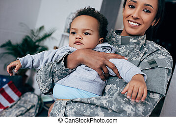 mother in military uniform with baby