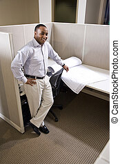 African American office worker standing in cubicle with floorplans