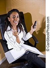 African American office worker with notebook and mobile phone