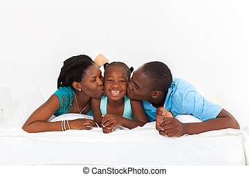 African American parents kissing daughter