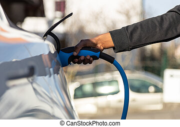 African American person plugin her EV electric car at the ...