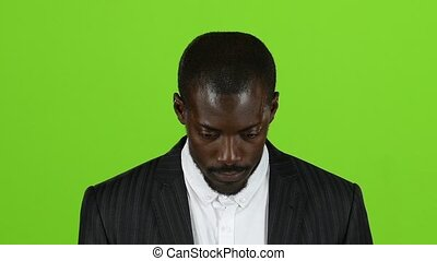 African american raises his gaze and looks. Green screen. Slow motion