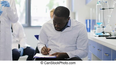 African American Researcher Making Notes While Female...