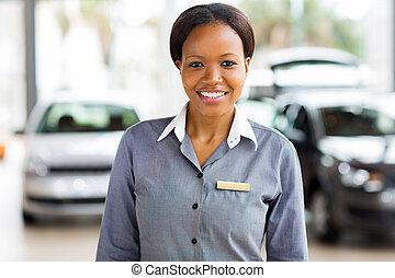 african american saleswoman standing at car dealership