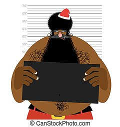 African American Santa at police station. Mugshot Black Santa gangster. Afro hairstyle and red Christmas hat.