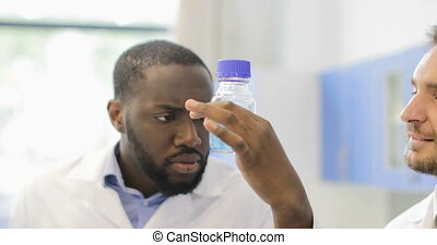 African American Scientist Man Analyzing Liquid In Bottle Discussing With Team Of Researchers Working In Laboratory