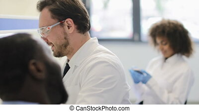 African American Scientist Man Discussing Analysis Of Experiment With Colleague, Mix Race Team Of Researchers Working In Laboratory Together