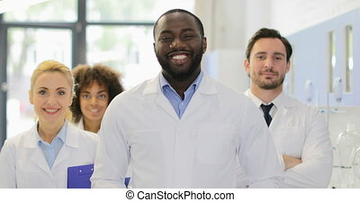 African American Scientist Man Happy Smiling Over Mix Race Team Of Researchers In Modern Laboratory Slow Motion 60