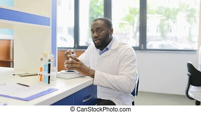 African American Scientist Man Using Mortar Box In Laboratory While His Colleague Working With Microscope Specialists Team