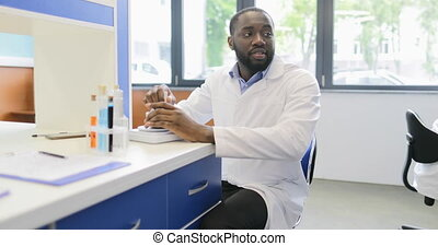 African American Scientist Man Using Mortar Box Working In Laboratory With Chemicals Examples Together With Group Of Doctors