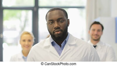African American Scientist Man Walk In Modern Laboratory Over Happy Smiling Team Of Researchers