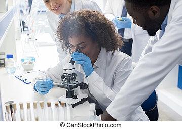 African American Scientist Using Microscope In Laboratory,...
