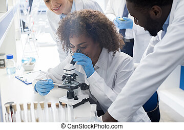 African American Scientist Using Microscope In Laboratory,...