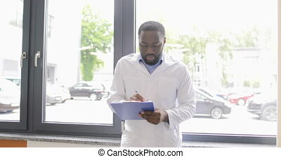 African American Scientist Walk In Laboratory Holding Documents Explain Experiment Plan To Colleague Working With Microscope