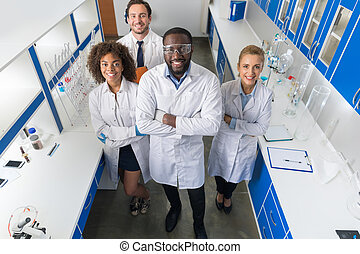 African American Scientist With Group Of Researchers In Modern Laboratory Happy Smiling, Mix Race Team Of Scientific Researchers In Lab