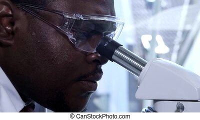 African-american scientist working in lab. Male doctor...