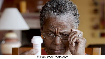 African American senior woman putting on glasses to read her prescription bottle