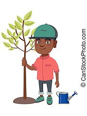 African-american smiling boy planting a tree.