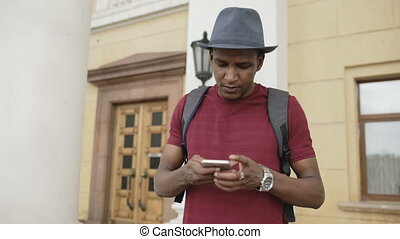 African american smiling tourist man using smartphone online...