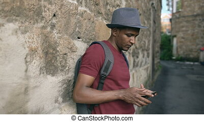 African american smiling tourist man using tablet online map...
