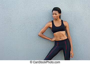 African american sports woman standing against gray background