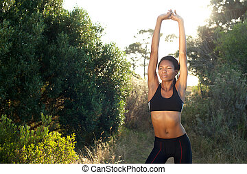 African american sports woman with arms raised outdoors