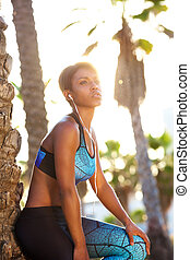 African american sporty woman relaxing with headphones
