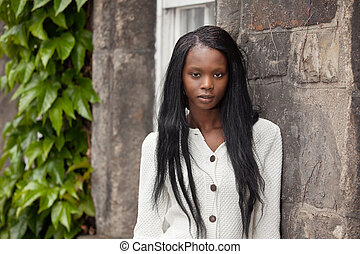 African American standing in front of stone wall