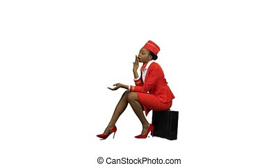 African American stewardess in a red suit sits on a suitcase and yawns . Alpha channel