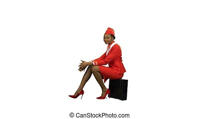African American stewardess in a red suit sits on a suitcase smile . Alpha channel