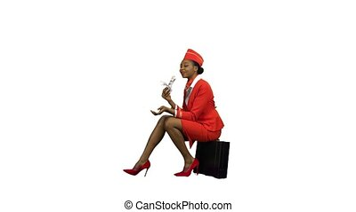 African American stewardess is sitting on a valise and counting paper money . Alpha channel