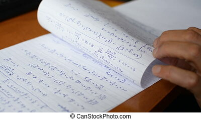African american student hand writing math calculus formulas text on exam paper