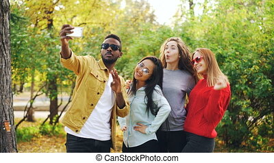 African American student is taking selfie with beautiful girls Asian and Caucasian standing in park, using smartphone and posing for camera. Youth and photo concept.