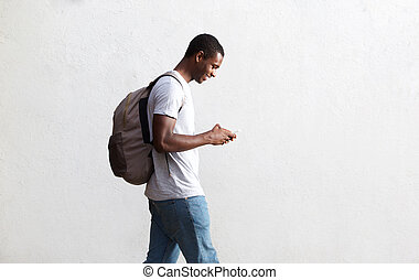 African american student walking with bag and mobile phone